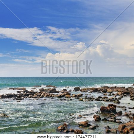 Scenic ocean coral reef near the shore and blue sky.