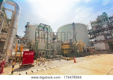 Industrial power plant red hose house big tank with light flare