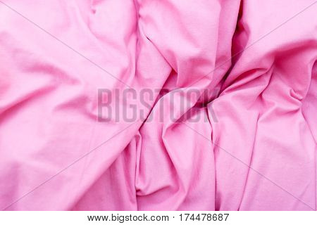 Fabric textures and patterns concept. Detailed closeup of pink creased quilt bedding