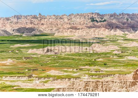View of eroded Badlands canyons with green prairie valley and shadows from clouds