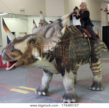 TUCSON, ARIZONA, FEBRUARY 20. The Tucson Expo Center on February 20, 2017, in Tucson, Arizona. A Grandmother and Granddaughter Ride a Styracosaurus at T-Rex Planet at the Tucson Expo Center in Tucson, Arizona.