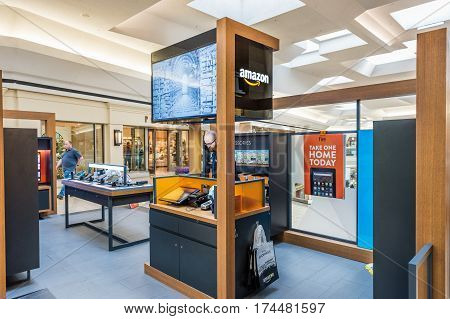 Fairfax USA - February 18 2017: Small Amazon store in mall with salesperson and products