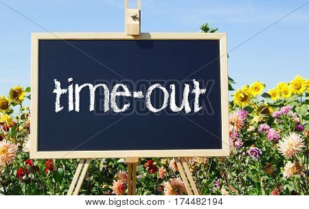 time-out - easel with text in the summer garden with flowers in the background