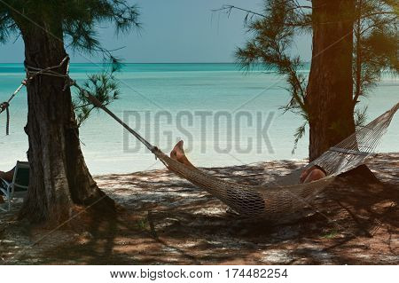 Bahamas beach with blue water man looking laying on hammock. Paradise vacation relaxing on hammock