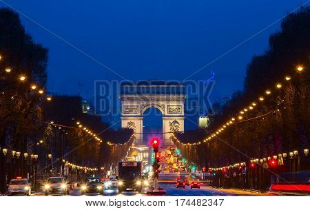 The Triumphal Arch andChamps elysees avenue at night Paris France.