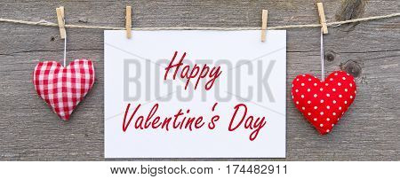 Happy Valentines Day - postcard with red hearts on wooden background