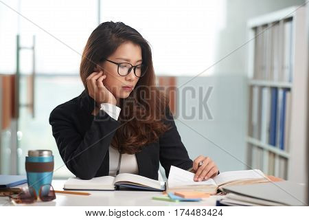 Vietnamese female law student reading a book and taking notes