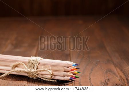 Set of sharp colorful pencils tied with wool rope on a wooden blank board. Background of brown table. Art and design. Artist. Drawing and painting.