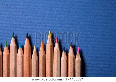 Row of colorful pencils on blue background. Uneven. Wooden pencils. Natural. Art and design. School and education. DRawing and painting.