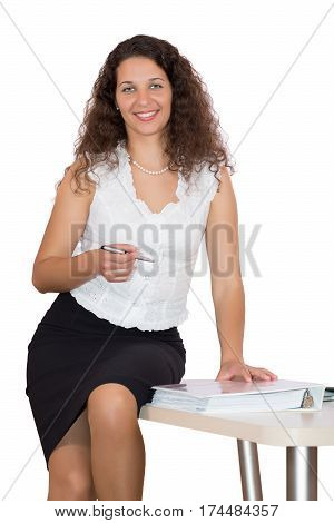 Beautiful smiling Business Lady in official dress code clothing sitting on office table with workbooks and stationery on white Background