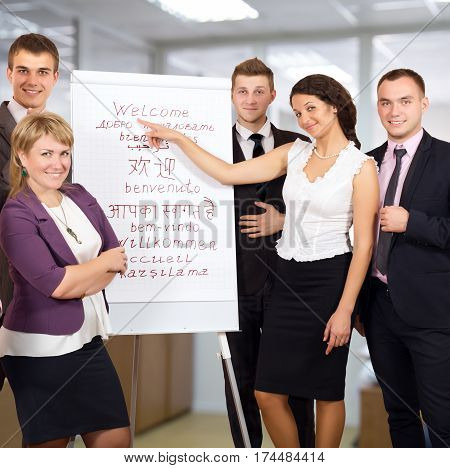 Group of smiling Business People welcoming Customers at flip chart with word WELCOME written in many different Languages Office Interior on Background