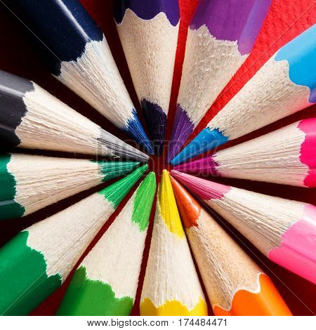 Circle formed by colored pencils on the red background. Center of the circle. Ary and design. Drawing and painting. Close-up view. Creative.