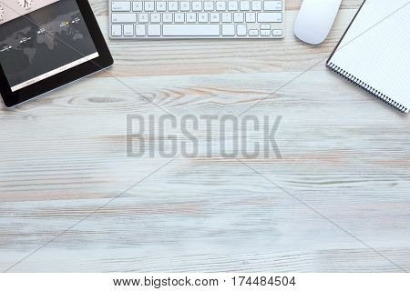 Composition with modern Electronics and Stationery Items in Wood Background Computer Keyboard Mouse Tablet PC and Notepad top View