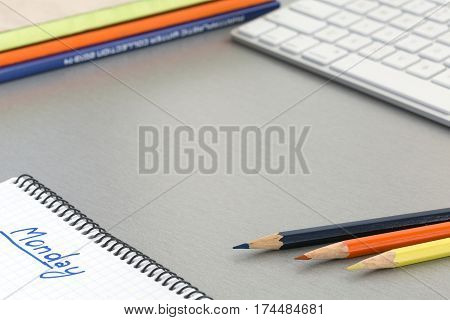 View of well ordered working Place on grey Table with Computer Keyboard Pencils Notepad with hand written word MONDAY