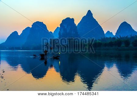 Silhouette of Man fishing with Cormorant Bird floating on traditional Boat in Central China River unusual shaped rocky Mountains and Morning Sky on Background