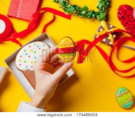 White Caucasian Female Hands Wraping Egg Shaped Cookie Near Things For Decoration On The Wonderful Y