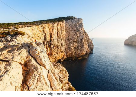 high cliffs and SEA in the sun at sunset, Neptune's Grotto in Sardinia, Italy