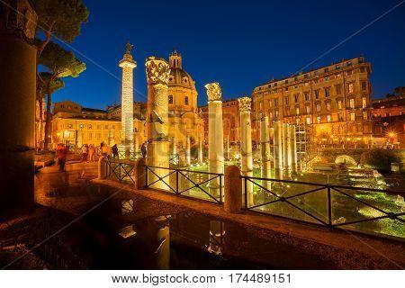 Forum - Roman ruins with column of Trajan illuminated at night, antique Rome Italy