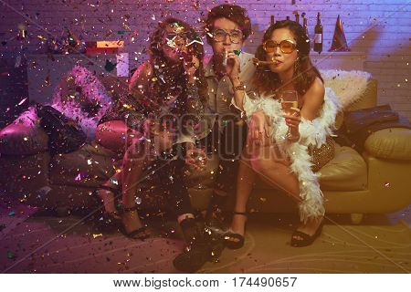 Vietnamese young people in funny glasses blowing in party whistles