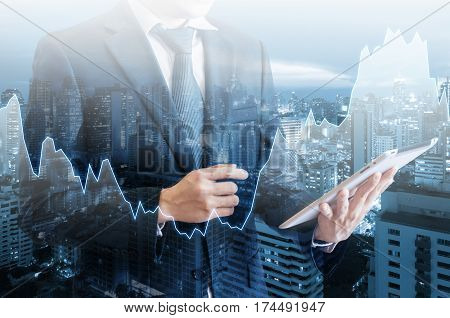 Double Exposure Of Professional Businessman Hold And Analyze Tablet With Cityscape And Financial / T