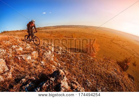 Cyclist Riding the Bike on the Mountain Rocky Trail at Sunset. Extreme Sports. Wide angle and fisheye. Cyclist in the helmet and with red backpack. Spring season in the countryside.
