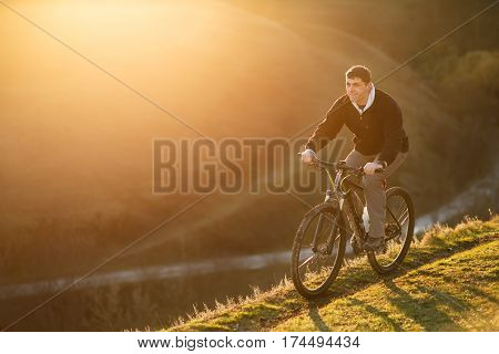 Cyclist riding on the top of a hill and watching the view. Cyclist in the black jacket. LAndscape with sunset and hill. Spring season. Travel in the countryside. Healthy lifestyle.