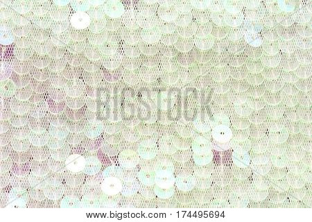 white sequins sewn on clothing details background textured closeup