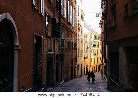 GENOA, ITALY - OCTOBER 23, 2016: Couple walking down the street of Genoa, one of Europe's largest cities on the Mediterranean sea and the largest seaport in Italy.