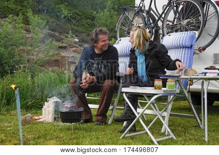 couple sitting in camping chairs in front of their camper and they are cooking on the barbecue