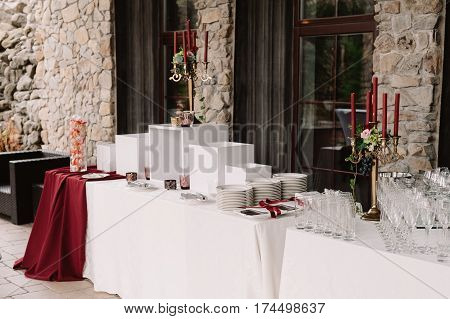 Wedding decoration of the table with red candles, candlesticks, white plates in the castle of love