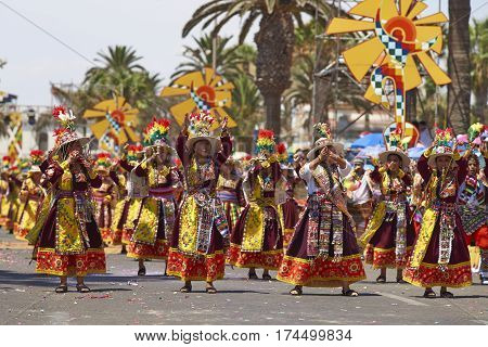ARICA, CHILE - FEBRUARY 10, 2017: Men and women of a Tinkus Dance Group dressed in ornate costumes performing a Tinkus dance during a street parade at the annual Carnaval Andino con la Fuerza del Sol.