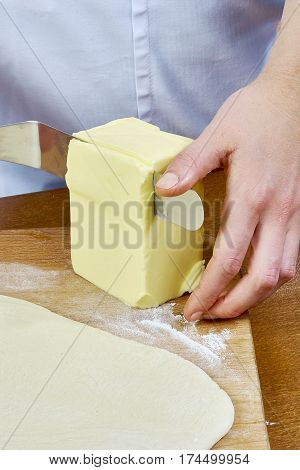 chef cuts a large piece of butter spread on the dough preparation cheesecakes