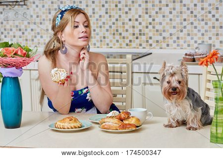 Young woman in flowery dress sits at table holding homemade cupcake, little dog sits near on table at kitchen.