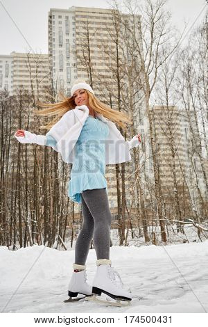 Young woman skates at outdoor skate rink in winter park against highrise buildings.