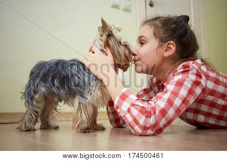 Girl rubs noses with yorkshire terrier, lying on floor in room.