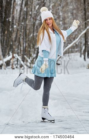Young woman in blue knitted dress, white fur mantle and hat at outdoor skate rink on skates in winter park.