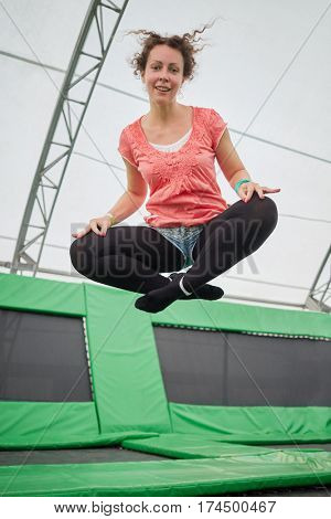 Young woman jumps on trampoline attraction in sitting position imitating levitation.
