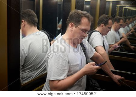 Man with smartphone in elevator cab, recursive view.
