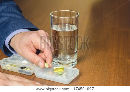 Glass of water vitamins and nutritional dietary supplement pills holding in hand of business man on work place close-up