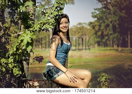 happy young woman posing in a tree in a sunny summer day