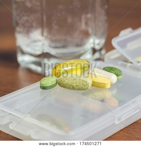 Mixed natural food supplement and vitamin pills on plastic container at wooden table