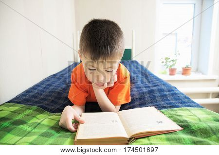 children education boy reading book lying on bed child portrait smiling with book education concept interesting storybook