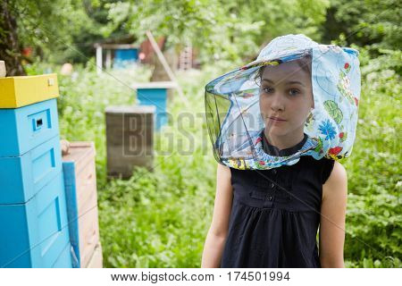 Teenage girl in hat with bee veil stands at apiary near beehives.