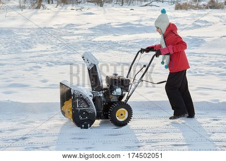 Girl moves snow thrower at snowy ground in park.