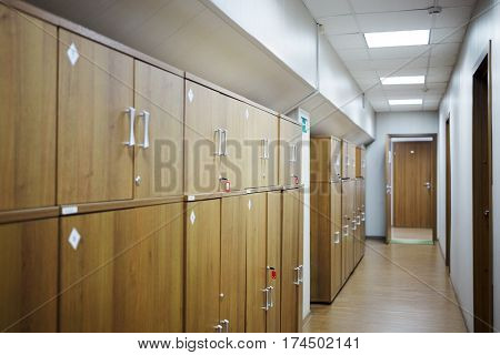 Corridor with wooden lockers along wall.