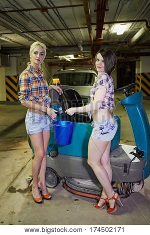 Two young women pose with bucket at floor scrubber machine in underground parking.
