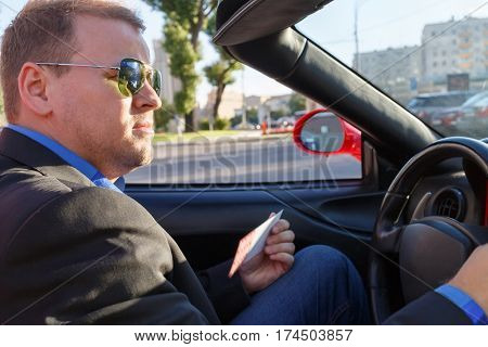 young businessman behind wheel driving luxury roadster, close-up