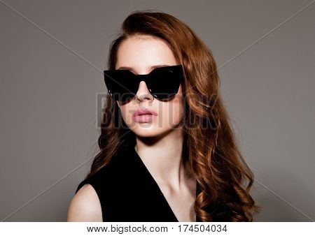 Young beautiful fashion model wearing black dress and glasses with no sleeves on grey background using hard light