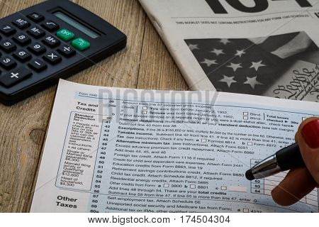 Tax preparation review holding pen with calculator on wooden table