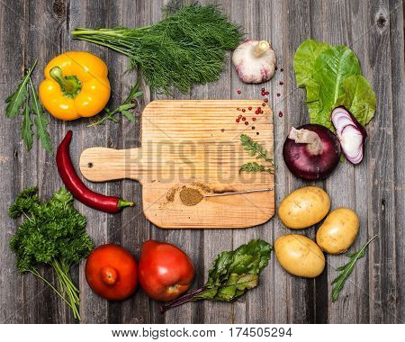 Colorful ingredients for vegetarian cooking on rustic weathered wooden table around empty cutting board with copyspace. Vegetables spices and herbs. Top view. Retro styled.